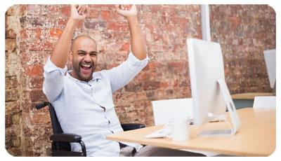 Illustration du handicap avec un homme en fauteuil roulant, heureux, levant les bras au ciel devant son ordinateur