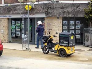 Photo d'un facteur et du Staby, scooter électrique plus ou moins ergonomique