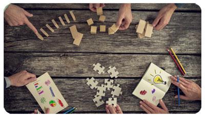 Illustration du management de la santé au travail : des mains devant des bouts de bois, des pièces de puzzle, des carnets avec des dessins et des crayons