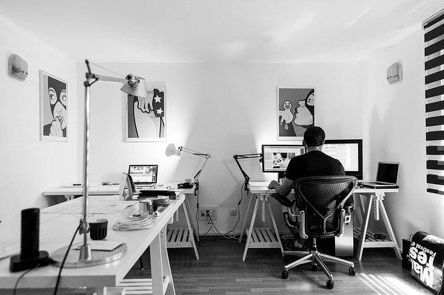 Photo D'une Personne Dans Un Milieu De Travail Bureautique, Avec Un Siège Ergonomique, En Noir Et Blanc