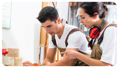 Illustration de prévention des risques professionnels : un homme et une femme, menuisier et menuisière avec une tenue de travail et un casque anti-bruit