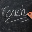 Illustration tableau noir sur lequel le mot coach est marqué à la craie pour parler des raisons de faire appels à des services de coaching