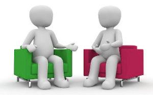 Coach et coaché discutent, chacun sur un canapé aux couleurs de Vicariance